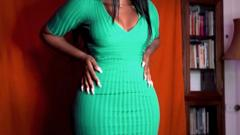 A lady in a green dress holding her hips.