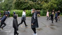 Children at schoo playing sports outside l in England during national lockdown