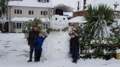 Family with snowman in garden