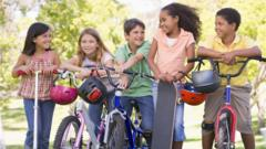 Children with scooters, skateboards and bikes