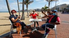 Italian tourists celebrate being able to sit on a terrace at promenade of Las Canteras beach