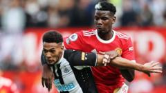 Manchester United's Paul Pogba and Newcastle's Joelinton fight for the ball