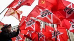 A boy in Moscow waves a communist flag during a rally to mark the 100th anniversary of the October 1917 revolution