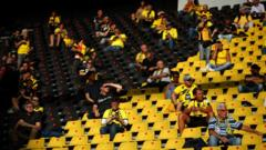 Fans at Borussia Dortmund watch from socially distanced positions