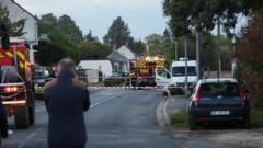 A man stands as French gendarmes and firemen work next to the site where an ULM crashed in Loches