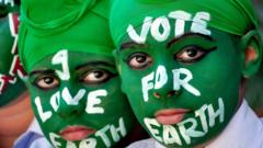 Indian students wearing green face paint with white writing