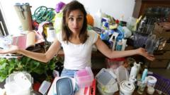 Anita Rani surrounded by plastic in a house