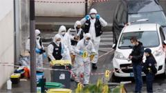 French forensic police investigators work at the site of the knife attack near the former Charlie Hebdo offices in Paris.