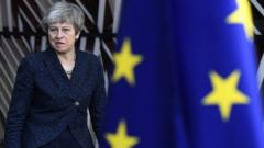 Theresa May and a Union Flag and an EU flag