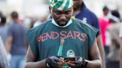 An #EndSars protester in a T-shirt with the hashtag against police brutality using his phone in Lagos, Nigeria - October 2020
