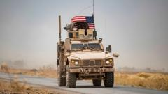 A US military vehicle drives in the vicinity of an oil field in in Syria