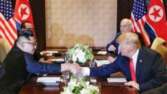 US President Donald J. Trump (R) and North Korean leader Kim Jong-un (L) shake hands across the table during the expanded bilateral meeting