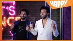 Mo Salah and his waxwork with the happy logo