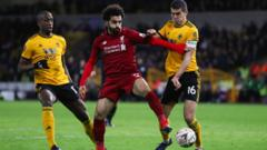 Mohamed Salah of Liverpool competes with Willy Boly and Conor Coady of Wolverhampton Wanderers during the Emirates FA Cup Third Round match between Wolverhampton Wanderers and Liverpool at Molineux