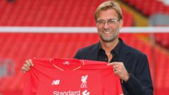 Jurgen Klopp holds up Liverpool shirt