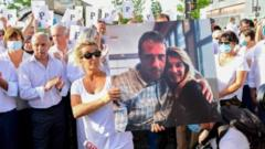 Wife of bus driver Philippe Monguillot, Veronique Monguillot (centre) holds a portrait of her husband during a march in Bayonne, France. Photo: 8 July 2020