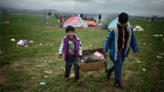Two boys carry fire wood at the Idomeni camp