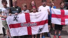 Young England fans hold flags up