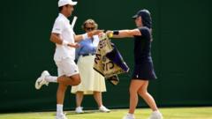 Ball girl hands towel to tennis player at Wimbledon