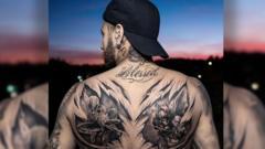Footballer Neymar displaying a back tattoo of Spiderman and Batman