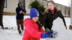 Ella and her sister Maddie making a snowman in Washington DC.