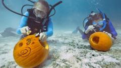 Divers carving pumpkins underwater