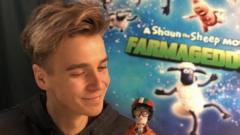 joe sugg holding a doll from sean the sheep