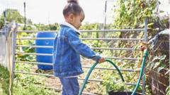 A girl adds water to a bucket