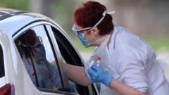 Medical staff are seen testing people at a coronavirus test centre in the car park of a theme park in Chessington