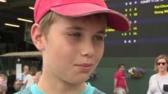 Boy in hat outside Wimbledon score board