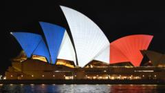 The iconic sails of the Sydney Opera House are lit in red, white and blue, resembling the colours of the French flag, in Sydney on November 14, 2015, as Australians express their solidarity