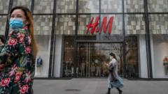 People walk by an H&M clothing store at a shopping area on 30 March 2021 in Beijing, China