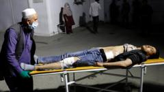 An Afghan man wheels an injured man in a hospital after a suicide bombing in Kabul, Afghanistan 24 October 2020