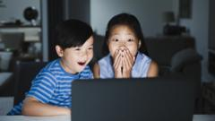 Two kids looking shocked at a laptop