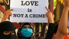 "A civil right activist holds a placard during a demonstration condemning the decision of various Bharatiya Janata Party (BJP) led state governments in the country for the proposed passing of laws against ""Love Jihad"" in Bangalore on December 1, 2020."