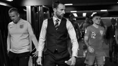 The England manager Gareth Southgate leads his players out of the tunnel. The image is in black and white.
