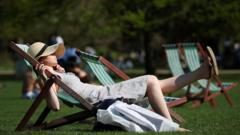 A woman lounges in the sunshine in a deckchair in St James Park, London, Britai