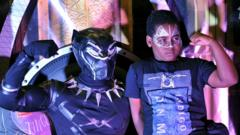 A fan poses with a cosplayer portraying a character from the 2018 US superhero film based on the Marvel Comics character, 'The Black Panther' pose in the Kenyan capital, Nairobi on February 14, 2018