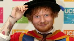 "Ed Sheeran tries on his robes before receiving an honorary degree from University Campus Suffolk in Ipswich for his ""outstanding contribution to music"". The 24-year-old singer-songwriter is to be awarded an honorary doctorate."