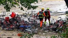 Rescuers walk past bikes in a flooded camp