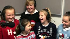 image of kids in christmas jumpers singing