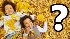 Two children smiling laying on leaves.