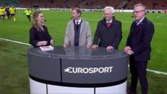 Four commentators stand around a table that reads 'Eurosport' as in the distance a group of Swedish players run to meet them.