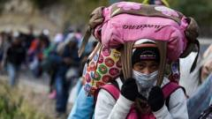 A Venezuelan migrant woman heading to Peru carries bags as she walks along the Panamerican highway in Tulcan, Ecuador, after crossing from Colombia, on August 21, 2018