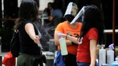 A hostess wears face shield while sprays antibacterial solution to a person before she enters in a restaurant of Zona rosa in Mexico City