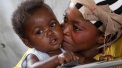 A infant sits in a hospital ward with her mother.