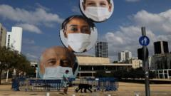 A sculpture decorated with images of people wearing face masks is seen at Habima Square, Tel Aviv, Israel (24 September 2020)