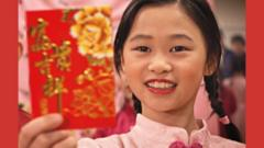 Young girl holding up a red envelope