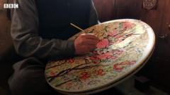 An artisan painting papier mache