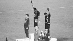 Athletes Tommie Smith and John Carlos - stand with their heads bowed and eyes closed, their hands raised with black gloves, and fists clenched.